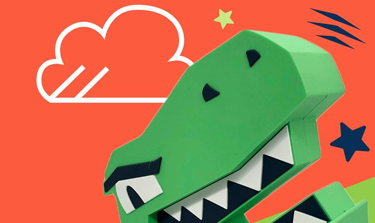 Na imagem aparece um carregador portátil coma a aparencia de uma cabeça de dinossauro bem fofo. O dinossauro tem a a boca aberta com espaço para colocar o celular dentro.